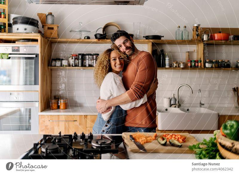Pärchen, das sich in der Küche umarmt. Lebensmitte Paar Liebe Essen zubereiten heimwärts gemütlich Kaukasier Partnerschaft vorbereitend Frau Glück Person Herd