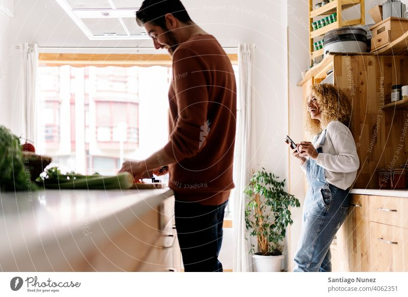 Pärchen lachend und in der Küche stehend. Lebensmitte Paar Liebe Essen zubereiten heimwärts gemütlich Kaukasier Partnerschaft vorbereitend Frau Glück Person