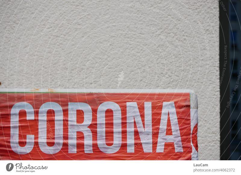 """Weißer Schriftzug """"Corona"""" auf rotem Hintergrund vor heller Hauswand Virus coronavirus Corona-Pandemie Coronavirus SARS-CoV-2 coronakrise weiß Wort Corona-Virus"""