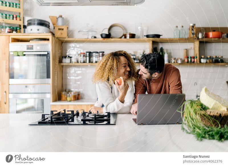 Ehepaar schaut in der Küche auf einen Laptop. Lebensmitte Paar Liebe Essen zubereiten heimwärts gemütlich Kaukasier Partnerschaft vorbereitend Frau Glück Person
