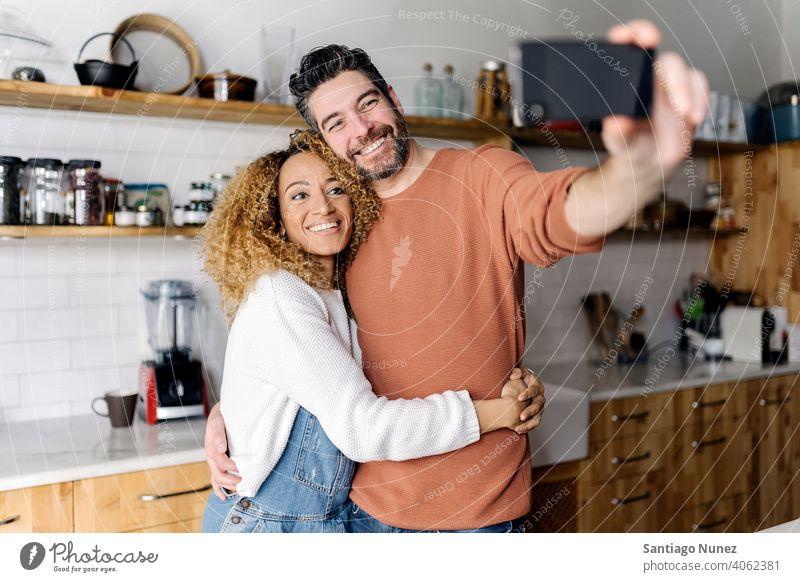Paar nimmt ein Selfie stehend in der Küche. Lebensmitte Liebe Essen zubereiten heimwärts gemütlich Kaukasier Partnerschaft vorbereitend Frau Glück Person Herd