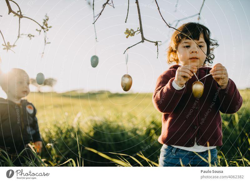 Bruder und Schwester spielen mit Ostereiern im Freien Geschwister Familie & Verwandtschaft Kind 2 1-3 Jahre Kaukasier Frühling Ostern Zusammensein Fröhlichkeit