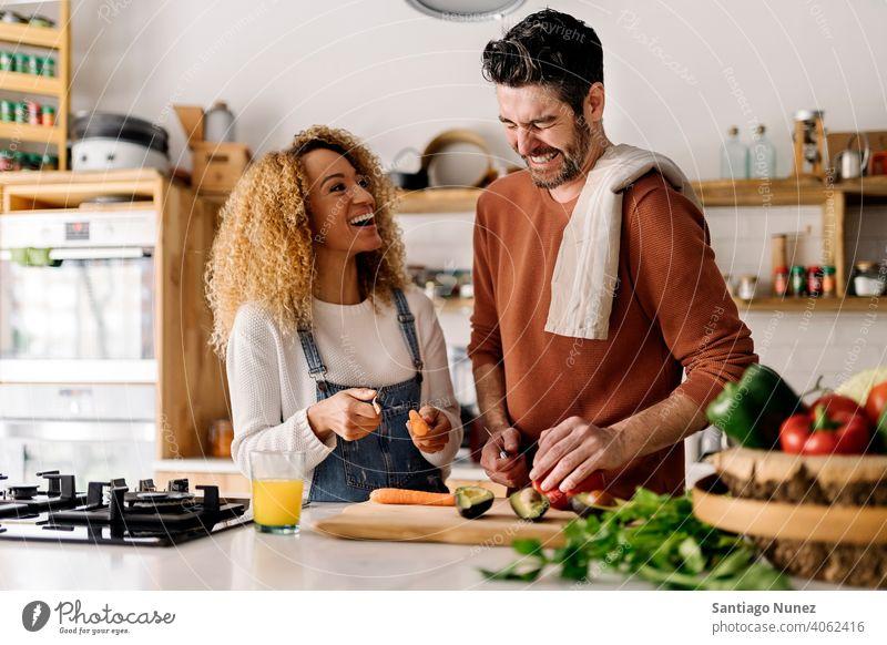Ehepaar bereitet Essen in der Küche vor. Lebensmitte Paar Liebe Essen zubereiten heimwärts gemütlich Kaukasier Partnerschaft vorbereitend Frau Glück Person Herd