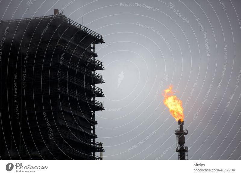 Löschturm vom Stahlwerk Thyssen-Krupp Kokerei in Duisburg. Dient zum Ablöschen von  heißem Koks . Daneben eine Gasfackel mit Gasflamme mit der überflüssiges Gas abgefackelt wird