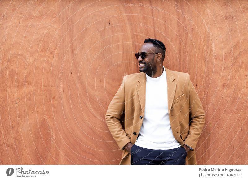 Gutaussehender schwarzer Mann, der an einer Wand lehnt und lächelnd zur Seite schaut. Afrikanisch Sonnenbrille Freizeit schreibend Porträt Großstadt urban