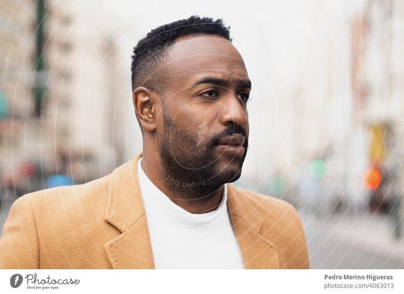 Gut aussehender afro-amerikanischer Mann, der sich auf die Lippe beißt und zur Seite schaut, in der Gran Via, Madrid. Lächeln Behaarung Hintergrund cool Stil