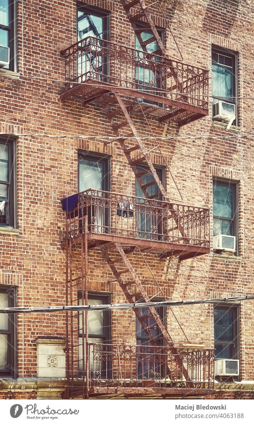 Altes Backsteinhaus Gebäude mit Eisen Feuerleiter, Farbe getönten Bild, New York City, USA. New York State Großstadt Feuertreppe Mietshaus Haus nyc Manhattan