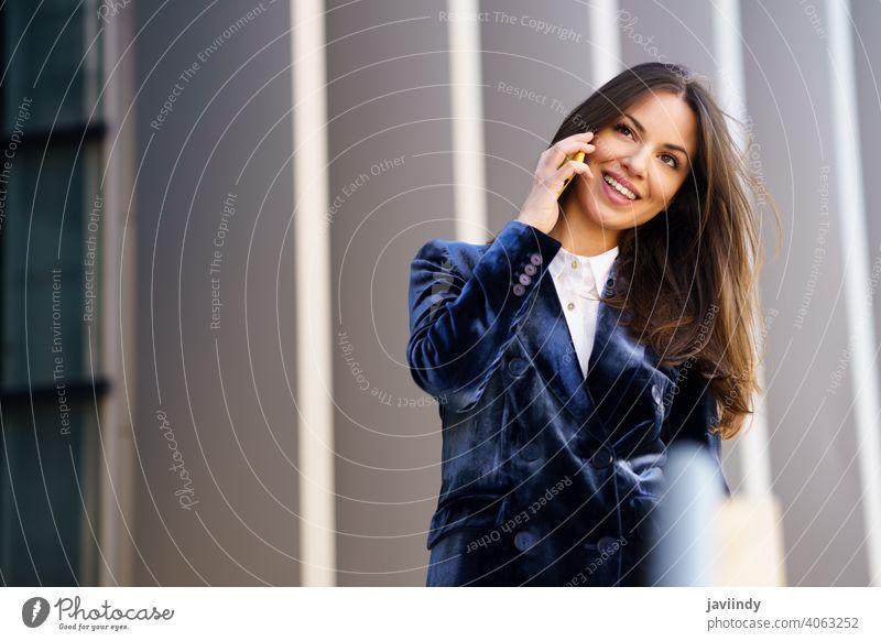 Business-Frau im blauen Anzug mit Smartphone in einem Bürogebäude. Geschäftsfrau Mädchen klug Telefon Person Gerät Lifestyle urban Hintergrund Dame elegant