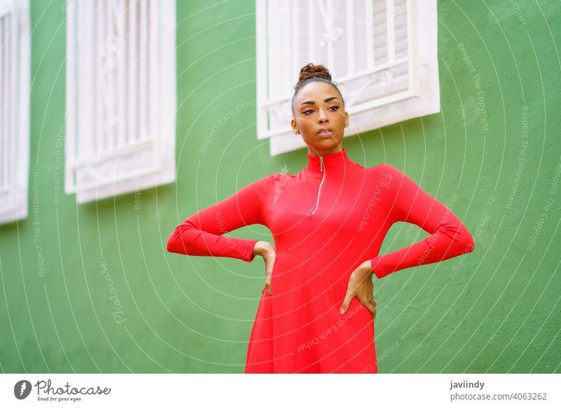 Junge schwarze Frau im roten Kleid vor einer grünen Wand Schleife ernst Frisur Behaarung Model Schönheit hübsch Porträt Mädchen jung Person Dame Sommer weiß
