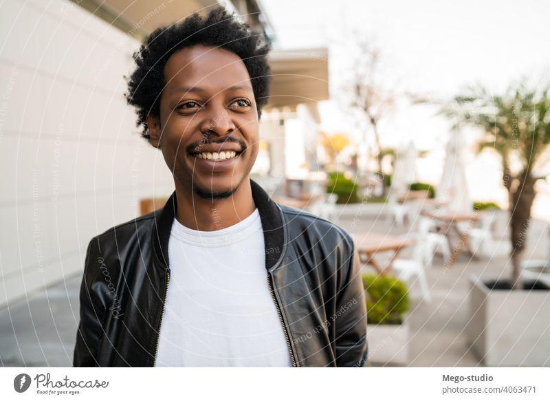 Porträt eines afroamerikanischen Mannes, der im Freien steht. Afro-Look Tourist Reisender Koffer Ausflugsziel Konzept Feiertag Tag Freude genießen Abenteuer
