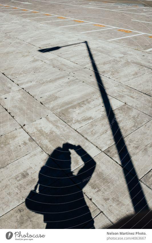 Silhouette eines Mannes, der ein Foto mit einer anderen Silhouette einer Stange macht schwarz auf weiß Fotografie künstlerisch kreativ Linien Zahlen Sonnenlicht
