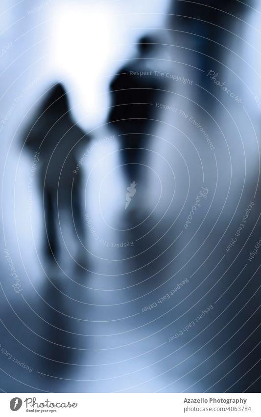 Silhouetten von Menschen, die sich in einem unterirdischen Gang bewegen abstrakt Erwachsener Kunst Hintergrund Blinken blau Unschärfe verschwommen Bokeh