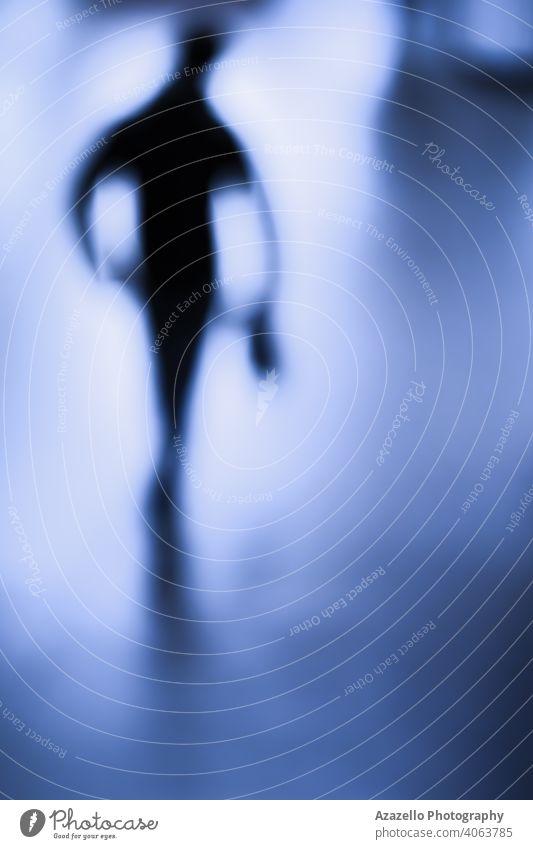 Unscharfes Bild eines Mannes. Männliche Figur in Unschärfe. abstrakt Erwachsener Kunst Hintergrund Blinken blau verschwommen Bokeh Business Konzept Menge