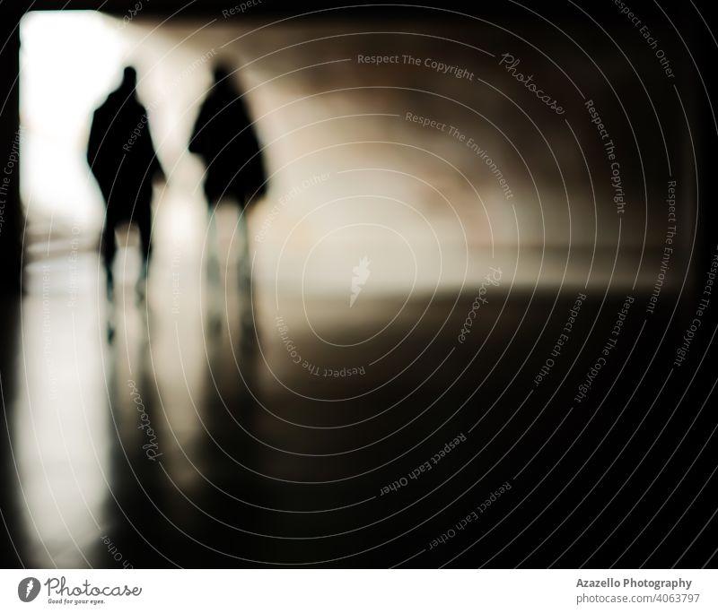 Menschliche Silhouetten in einem unterirdischen Gang. Menschen in Unschärfe. abstrakt Erwachsener Kunst Hintergrund verschwommen Bokeh Business Konzept Paar