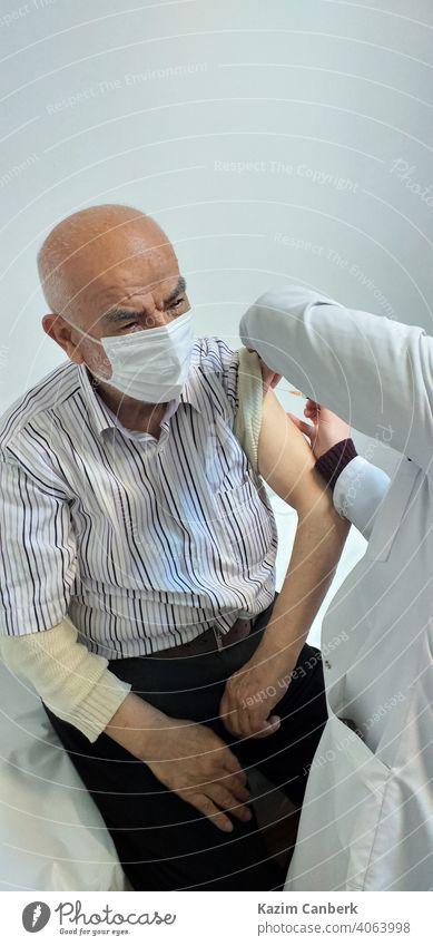 Alter türkischer Mann, der von einer Krankenschwester in einem Krankenhaus den Impfstoff Covid 19 in den Arm gespritzt bekommt Bund 19 Schuss Einspritzung