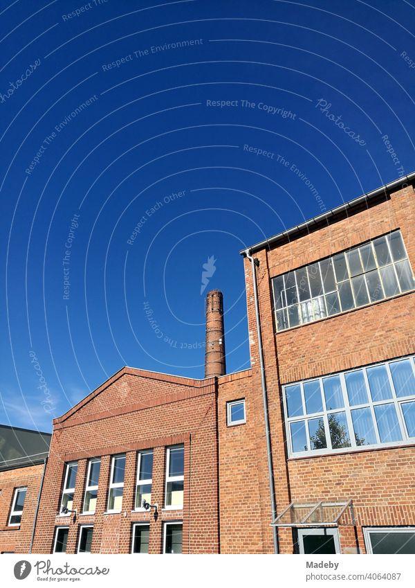 Alte Fabrikgebäude und hoher Fabrikschornstein mit schöner Fassade vor blauem Himmel bei Sonnenschein in der Hansestadt Lemgo bei Detmold in Ostwestfalen-Lippe