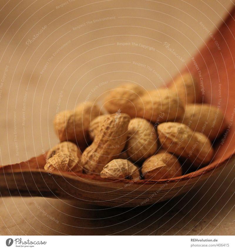 Eine Erdnuss bitte Lebensmittel braun Schalen & Schüsseln Hülle beige Holz Natur natürlich Menschenmenge viele Knabbereien Snack Farbfoto Innenaufnahme