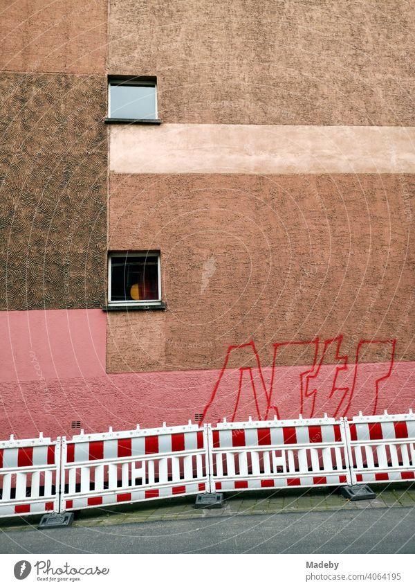 Fassade mit zwei Fenstern und Farbestaltung in Rosa und Brauntönen mit Graffiti und Bauzaun in Offenbach am Main in Hessen Anstrich Putz Farbgebung