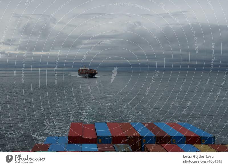 Blick auf ein Containerschiff von einem anderen Schiff aus, das sich dem Hafen von Vancouver, Kanada, vom Pazifischen Ozean im Bereich der Salish Sea nähert.