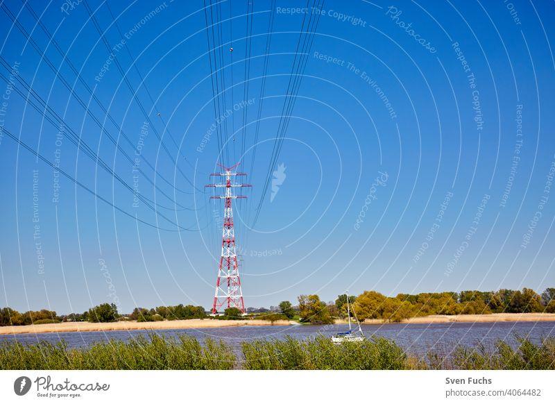 Rot-weiße Strommasten stehen an der Elbe strommast energie stromleitung energiewende deutschland hamburg elektrizität kraft emporragen himmel kabel electrik