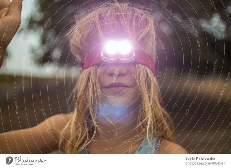 Mädchen mit Kopftaschenlampe im Freien Spaß Menschen Sommer Camping retro altehrwürdig Taschenlampe reisen Abenteuer Kindheit Stirnlampe Scheinwerfer Abend