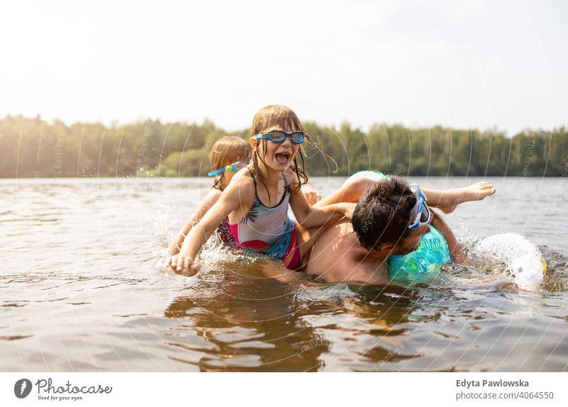 Vater und Kinder haben Spaß im See Sommer Urlaub reisen Wasser Lachen Tag sonnig platschen Tropfen Spielen spielerisch aktiv Strand schön Kindheit Familie