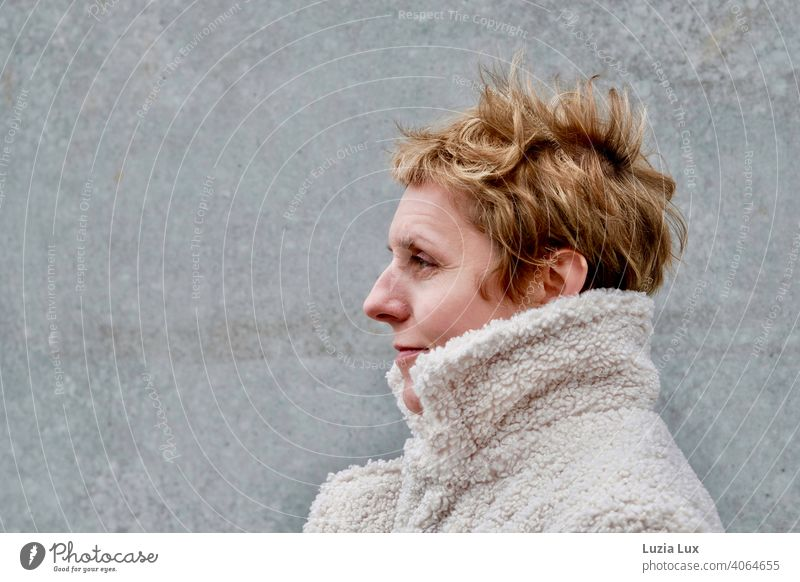 stürmisch: eine hübsche Frau mit sehr kurzem, blondem Haar im Profil, eingekuschelt in einen hellen Mantel. Porträt kurzhaarig Erwachsene feminin elegant