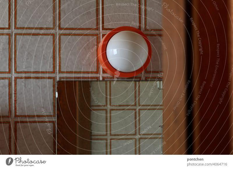 Blick in ein Badezimmer aus den 70ern. retro. toilette, fließen, orange badezimmer tür seventies Häusliches Leben 70er Jahre Design lampe Vergangenheit