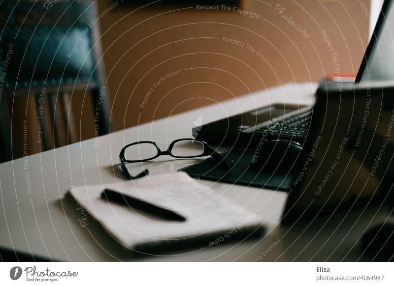 Arbeitsplatz im Homeoffice: Schreibtisch mit Laptop, Notizblock und Brille Home Office Stift arbeiten Notebook Büro zuhause dunkel