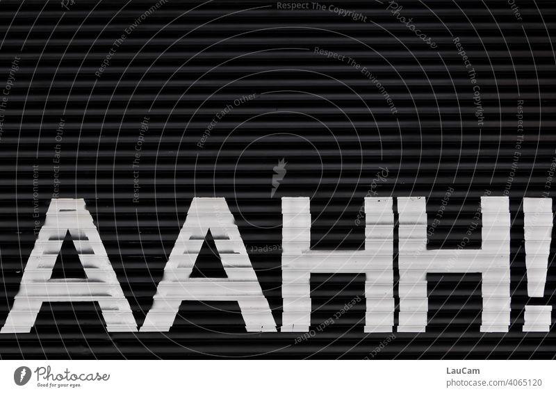 """Weißer Schriftzug """"AAHH!"""" auf einem schwarzen Hintergrund weiß schwarzweiß Schriftzeichen Buchstaben Wort Lautmalerei lautmalerisch Typographie Text"""