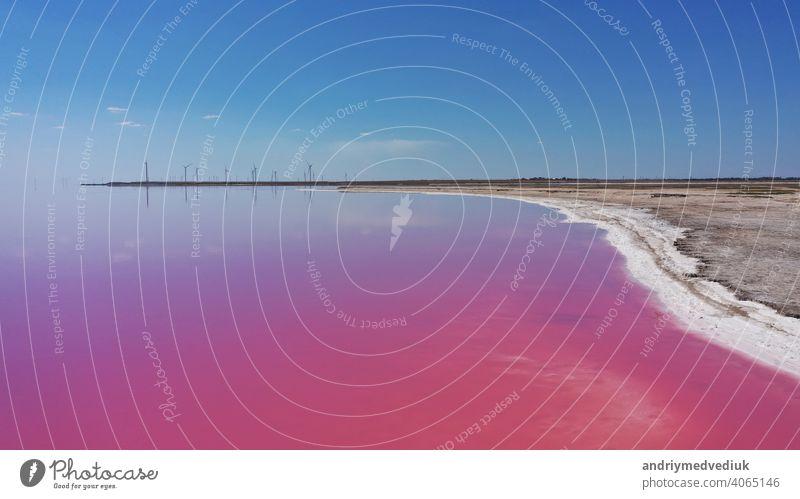 Aerial Drohne Top-Down-Foto von einem natürlichen rosa See, blauer Himmel und Küste Kuyalnik in Odessa, Ukraine. Der See färbt sich aufgrund von Salzen und kleinen Krebstieren (Artemia) im Wasser natürlich rosa
