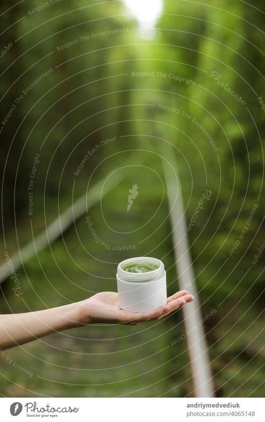 Junge weibliche Hand halten ein Glas grüne natürliche Creme für Gesicht oder Körper. organische natürliche Hautpflegeprodukte auf grünen natürlichen Hintergrund. Verpackung von Lotion oder Creme. Schönheit Kosmetik Hautpflege Konzept.