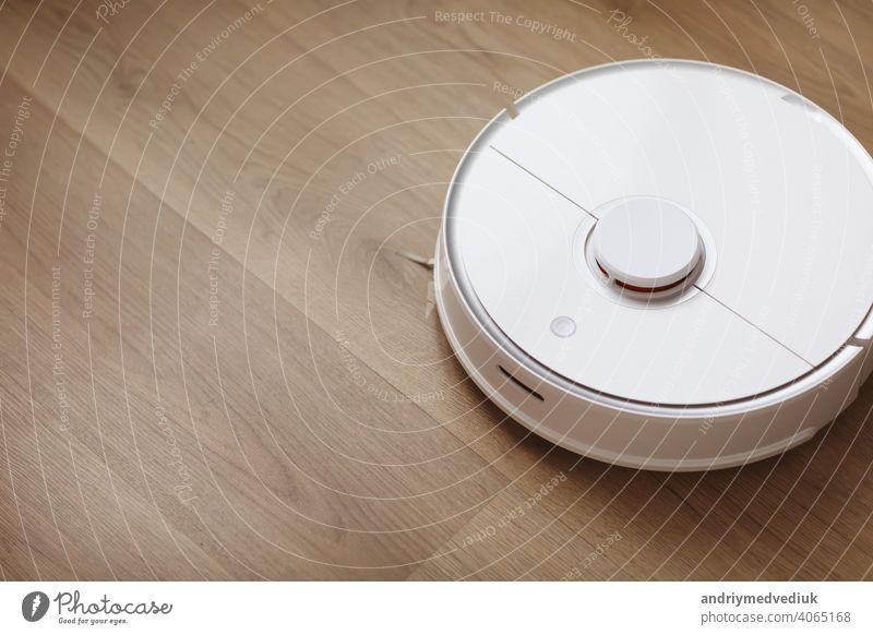 Staubsaugerroboter reinigt die Wohnung automatisch zu einer bestimmten Zeit. weißer Staubsaugerroboter. home cleaning. Smart Home. Selektiver Fokus Vakuum