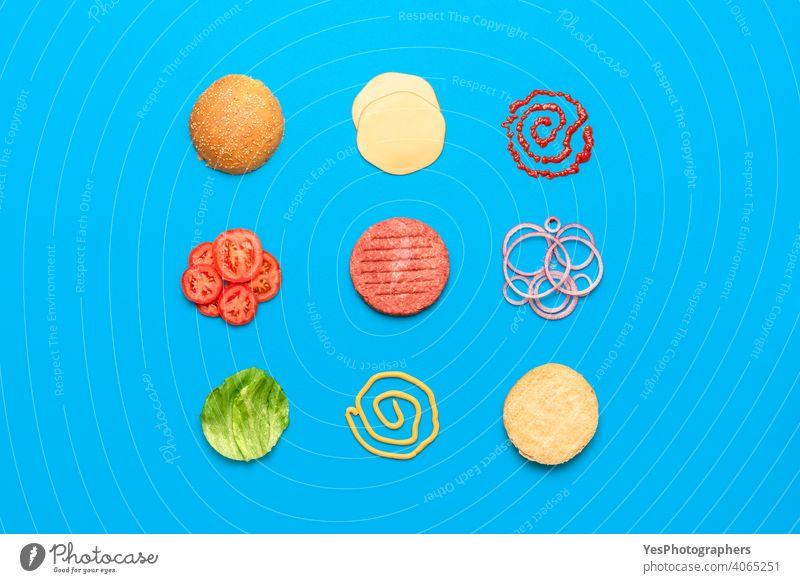 Burger Zutaten Draufsicht isoliert auf blauem Hintergrund obere Ansicht ausgerichtet angeordnet Rindfleisch Brot Brötchen Cheddar Käse Cheeseburger farbig