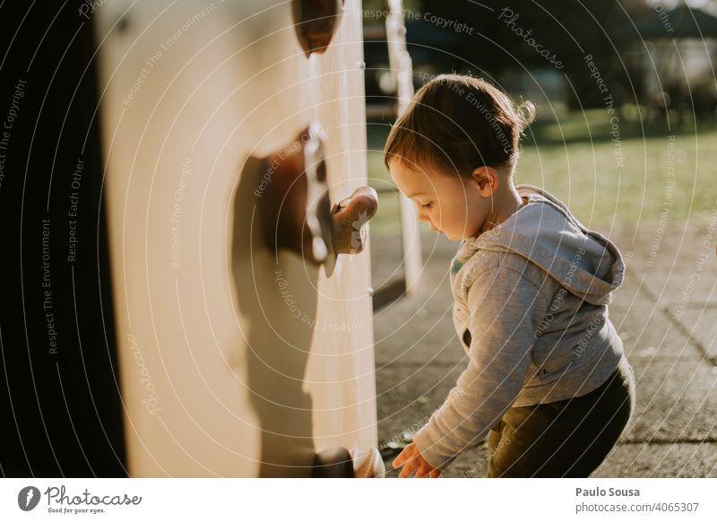Kind spielt auf dem Spielplatz Kaukasier 1-3 Jahre authentisch Spielen Kletterwand Park Fröhlichkeit Glück Kleinkind Tag Kindheit Mensch Farbfoto Außenaufnahme
