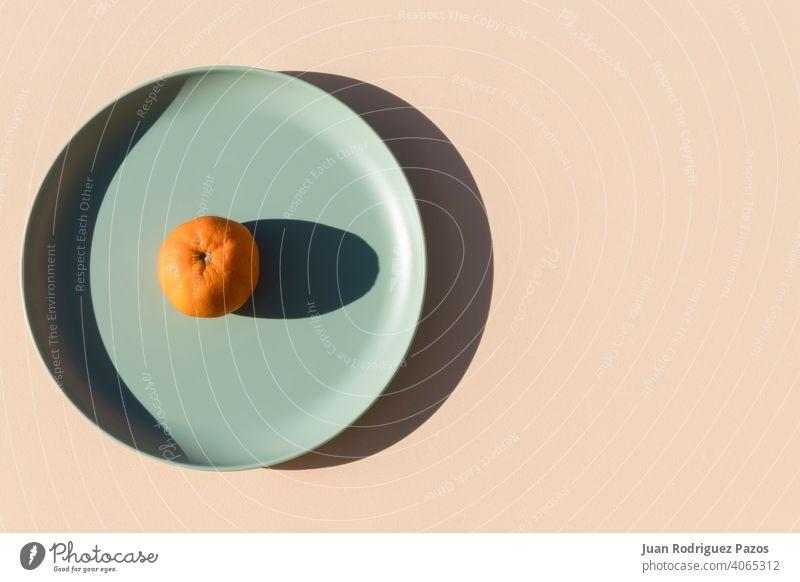 Minimalistisches Bild einer Mandarine auf einem hellgrünen Teller mit einem beigen Hintergrund. Ansicht von oben. kreativ Frucht sehr wenige orange