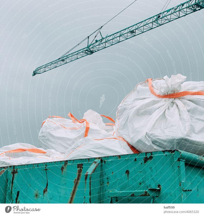 Bauschutt in Säcken auf einem Container Sondermüll Baustelle Kunststoff Müllsack entsorgen Abfall Müllentsorgung Müllbehälter wegwerfen Umwelt Müllabfuhr