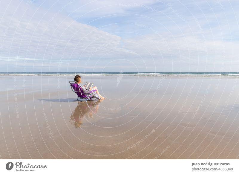 Frau liest ein Buch auf einem Stuhl sitzend an einem einsamen Strand MEER lesen im Freien soziale Distanz einsamer Strand Sitzen sich[Akk] entspannen friedlich