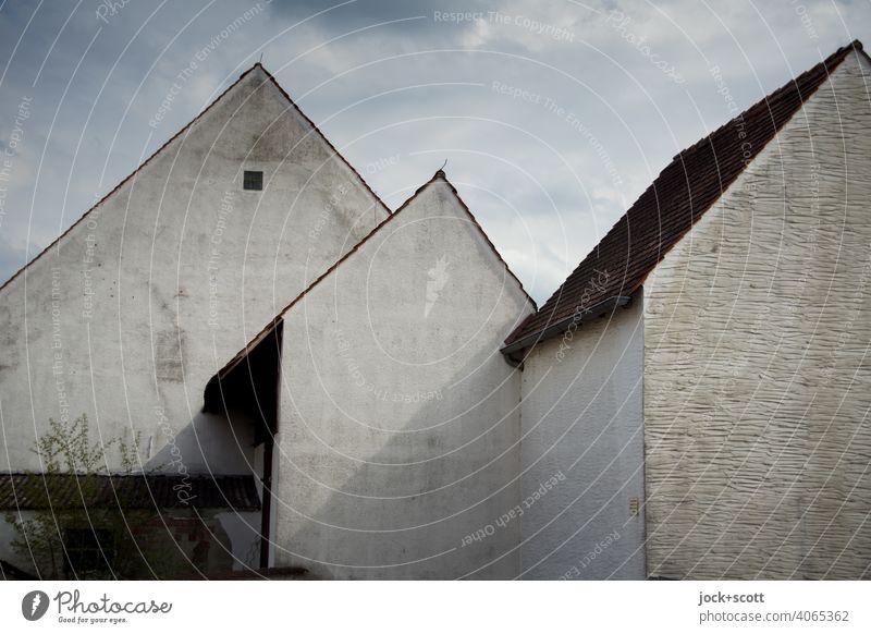 3 markante Haustypen mit Satteldach Silhouette Hauswand Architektur Strukturen & Formen Franken Gedeckte Farben fensterlos Rückseite Wolken diesig Putzfassade