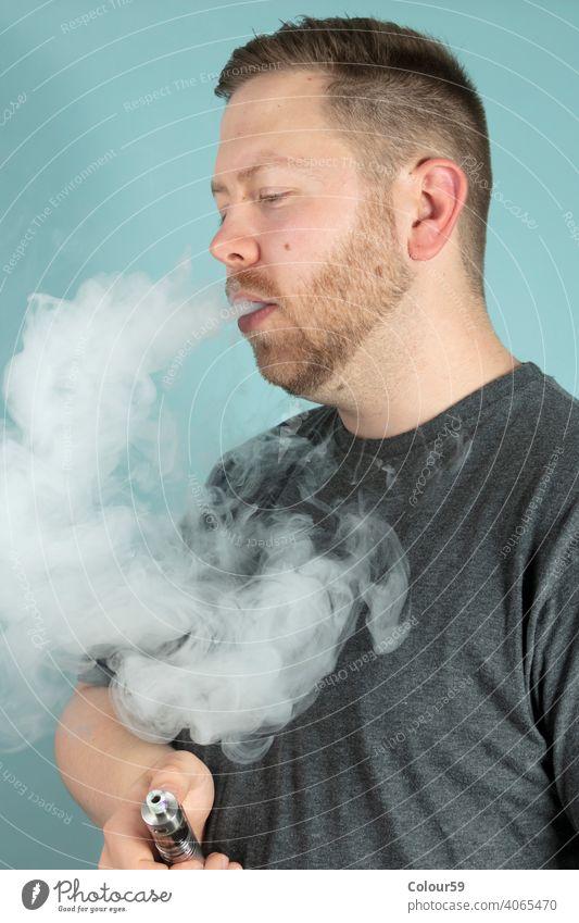 Junger Mann, der eine E-Zigarette raucht süchtig machend Cloud elektronisch ausatmend Nikotin Rauch Raucherin Rauchen Stimulans ungesund Raps Verdampfer Laster