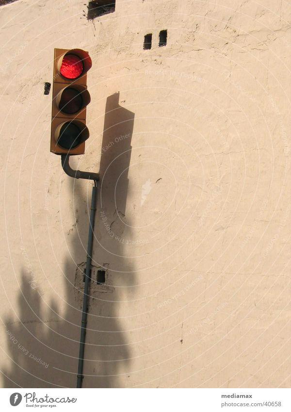 Rotlicht Ampel rot Mauer beige stoppen Dinge Schatten warten