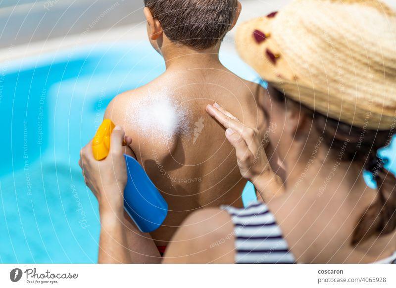 Mutter trägt an einem Sommertag Sonnenschutzmittel auf den Rücken ihres Sohnes auf bewerben anwendend Strand Krebs Kind Kindheit Sahne Creme Familie Frau Hand