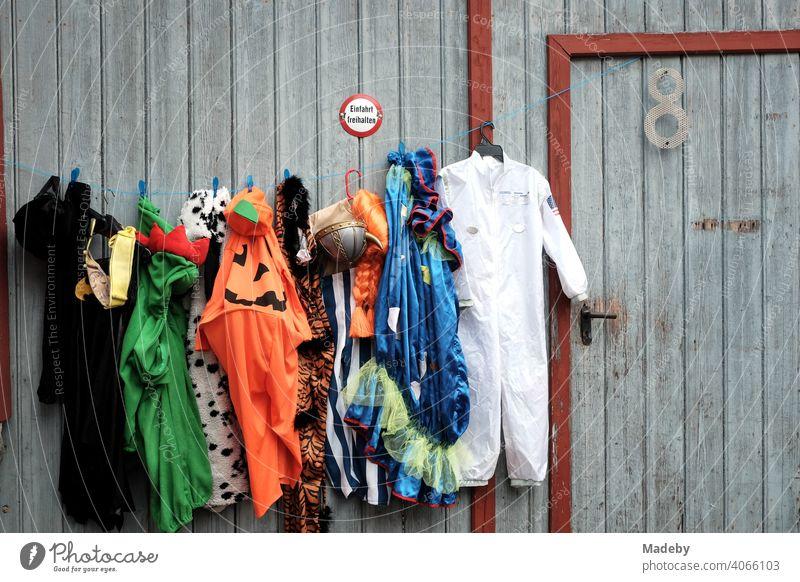 Bunte Kleider und Kostüme an einem alten grauen Scheunentor auf dem Flohmarkt bei den Golden Oldies in Wettenberg Krofdorf-Gleiberg bei Gießen in Hessen Mode