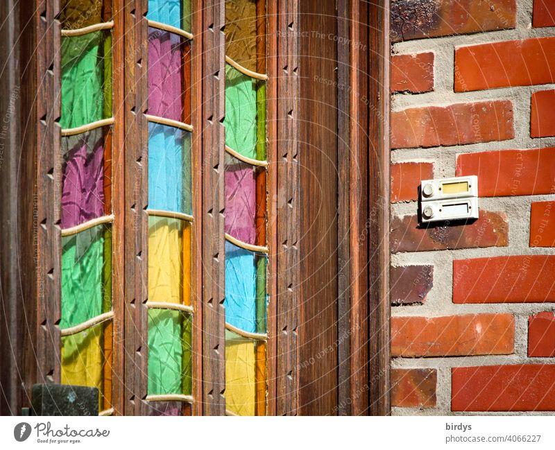 Alte hölzerne Hauseingangstür mit bunten Glasscheiben, Backsteinwand mit Klingel.Eingang Tür Haustür Holztür mehrfarbig freundlich Eingangstür alt lila gelb
