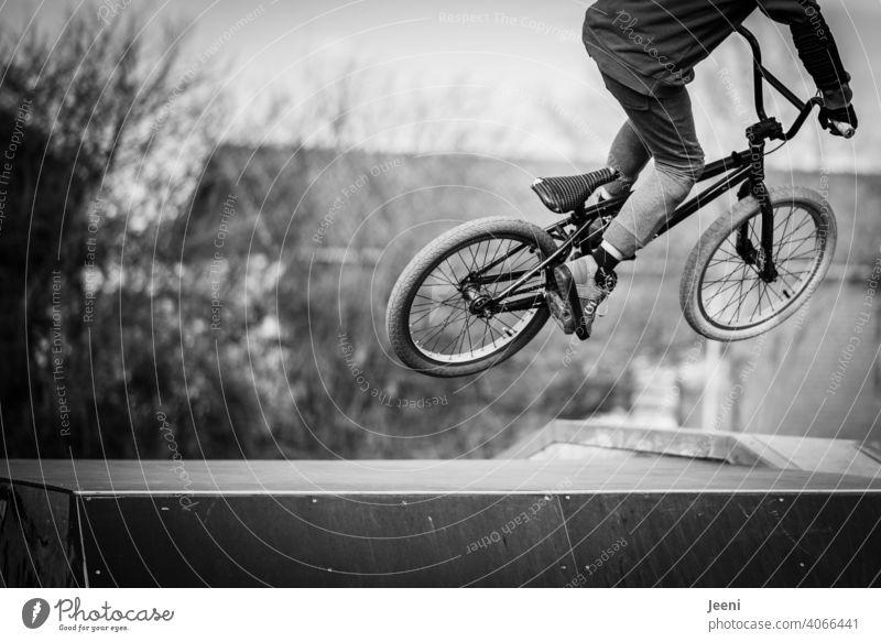Jugendlicher springt mit dem BMX Fahrrad über eine Rampe Stunt springen hoch hinüber jugendlicher Kind Kindheit jugendzeit Jugendlichkeit Sport Bewegung