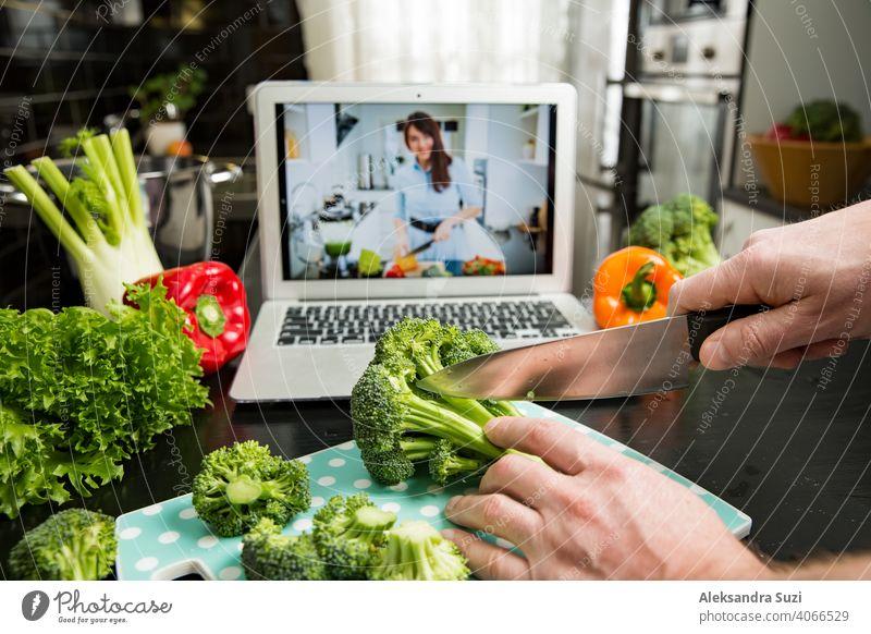 Schöne glückliche Frau Streaming Broadcast-Video-Blog über leckere und gesunde Lebensmittel aus der Küche zu Hause. Gesunder Lebensstil und soziale Medien. Mann beobachten Video Rezept auf Laptop und Kochen zu Hause.