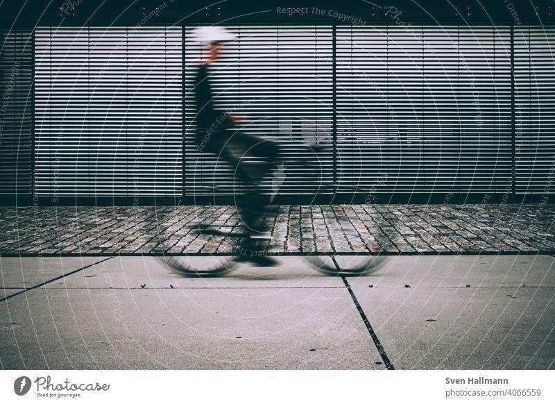 Verschwommener Radfahrer  vor geschlossener Jalousie Fahrrad Minimalismus Silhouette abstrakt bremerisch Langzeitbelichtung linien urban Radfahren Biker