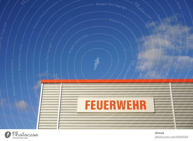 """Teilansicht eines Zweckgebäudes mit Metallverkleidung und der Aufschrift in rot """"FEUERWEHR"""" vor blauem Himmel mit Schönwetterwolken / Rettungsdienst / Notruf 112"""