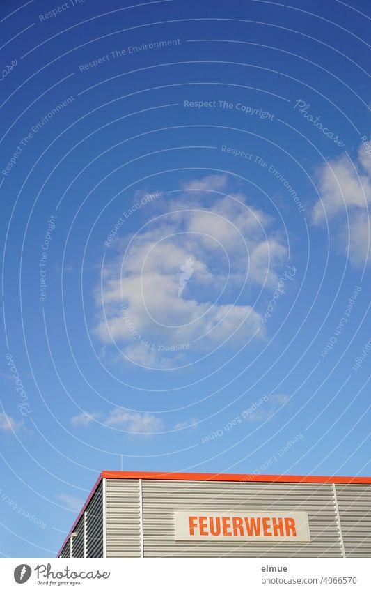 """Zweckgebäude mit grauer Wellblechverkleidung und einem Schild mit roter Aufschrift """"FEUERWEHR""""  vor blauem Himmel mit Schönwetterwolken / 112 / Rettungsdienst"""