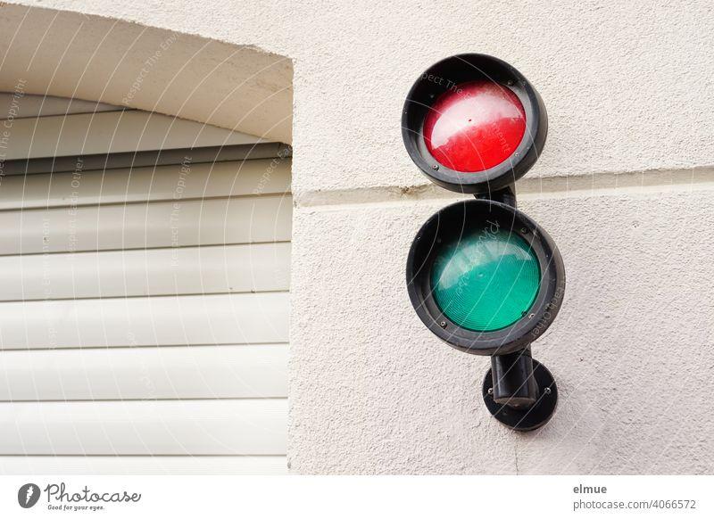 kleine rote und grüne Signallampen an der Hauswand neben einer geschlossenen Garageneinfahrt mit Rolltor / Ampel Ampelverkehr Einfahrt Hauseinfahrt Gebäude